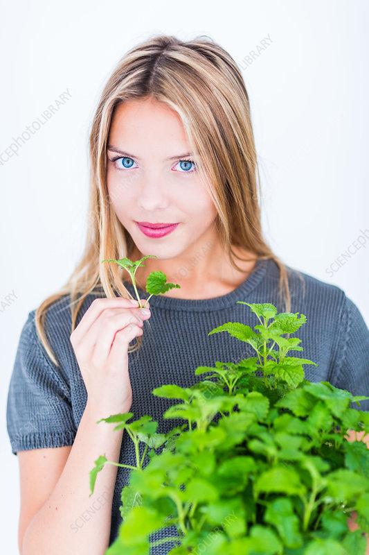 Woman inhaling lemon balm fragrance