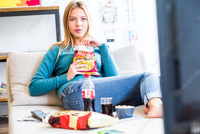 Woman snacking while watching TV