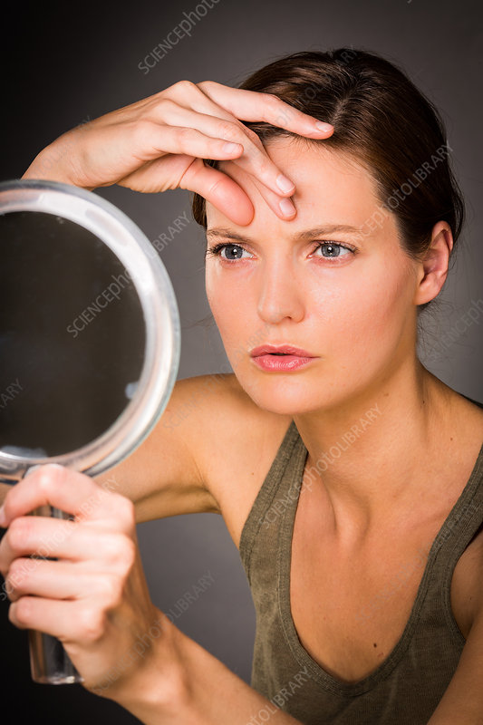 Woman checking her face in the mirror