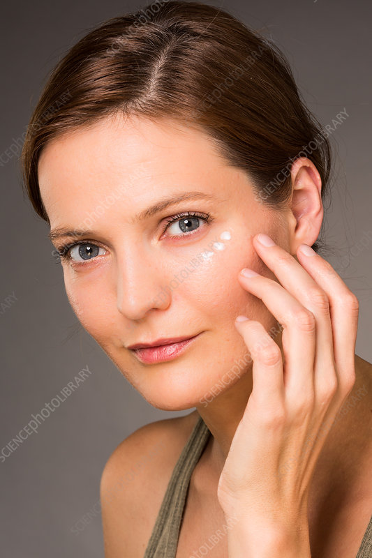 Woman applying anti-wrinkle cream around the eyes