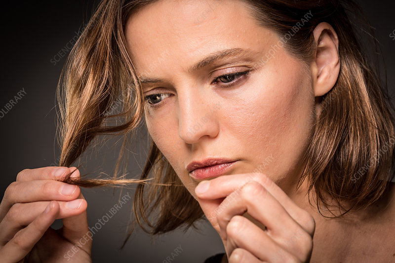 Woman inspecting the tip of her hair
