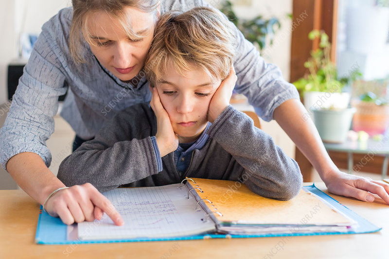 Boy doing homework with his mother