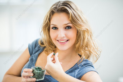 Woman taking a tablet of green algae