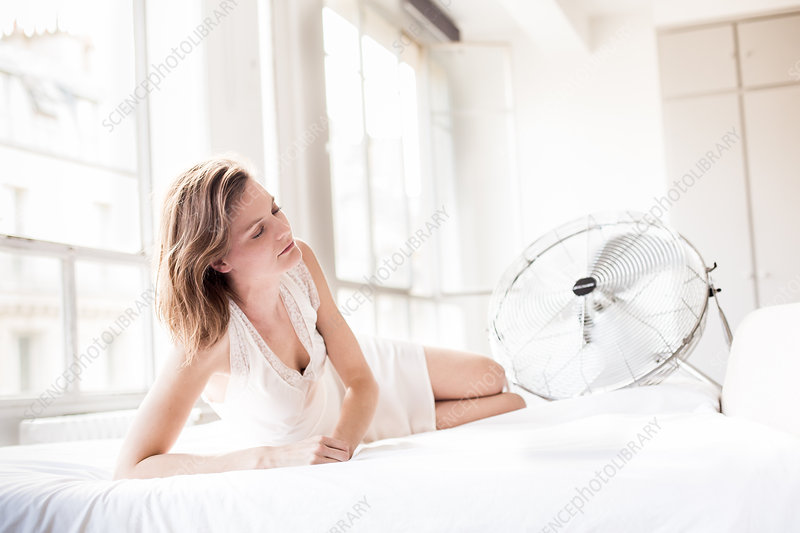 Woman in front of electric fan