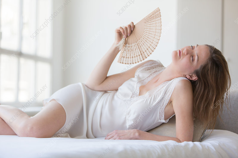 Woman cooling her face with a fan