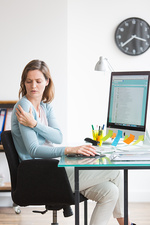 Woman at work suffering from shoulder pain