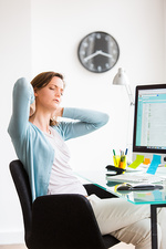 Woman suffering from neck pain in office