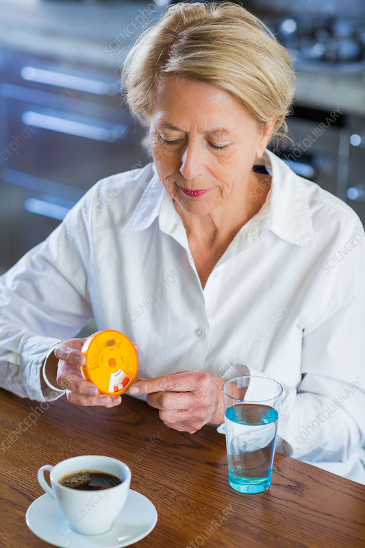 Woman taking medicine from a pillbox