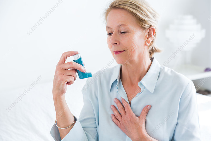 Woman using an aerosol inhaler