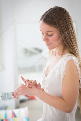 Woman applying cream on her hands