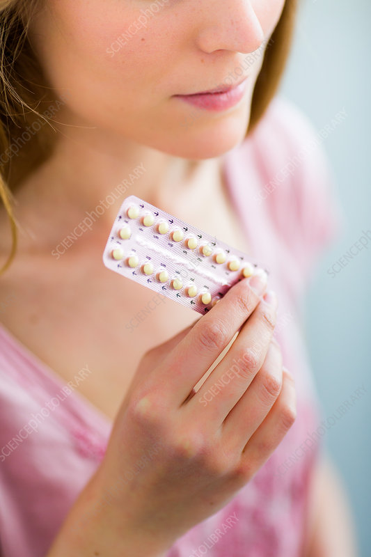 Woman holding oral contraception pills