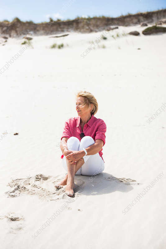 Senior sitting on the sand
