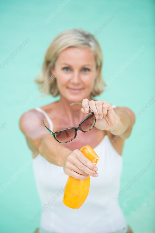Woman holding sunglasses and sunscreen