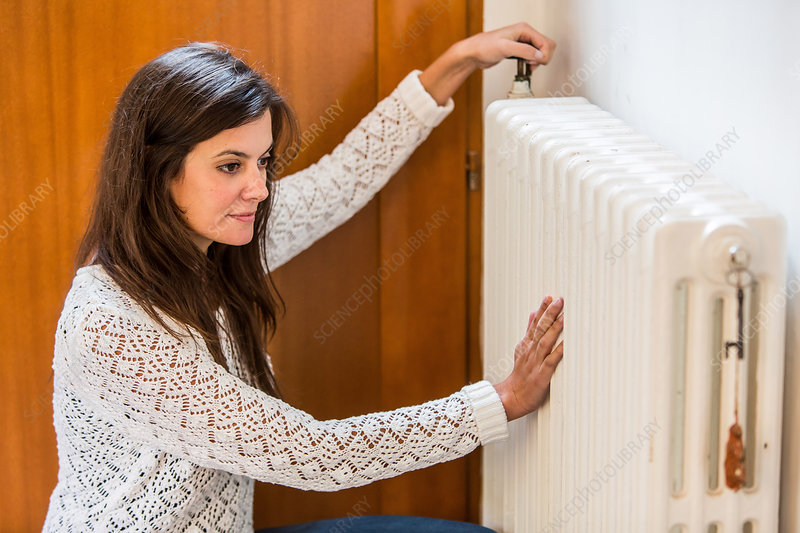 Woman adjusting a thermostatic radiator valve