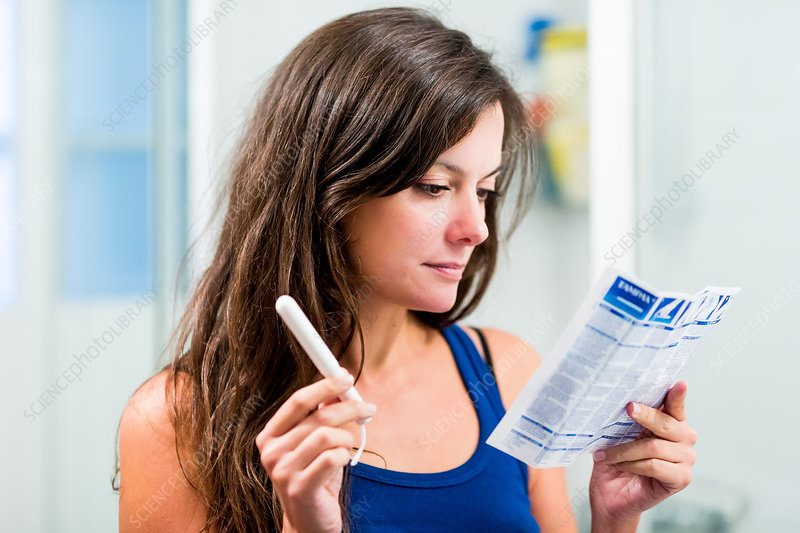 Teenage girl reading tampons instructions sheet