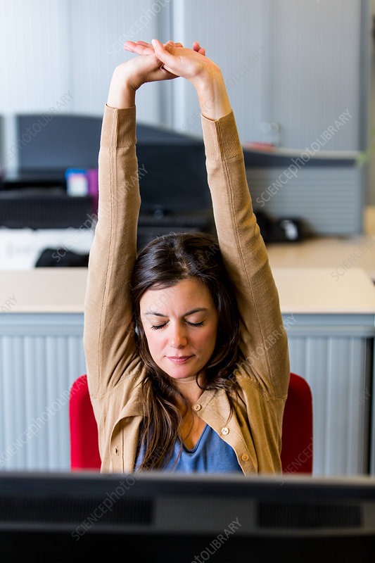 Woman stretching arms at work