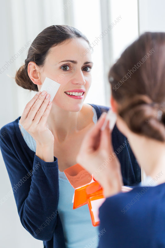 Woman using blotting paper on oily skin