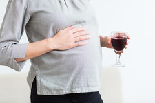 Pregnant woman with a glass of wine