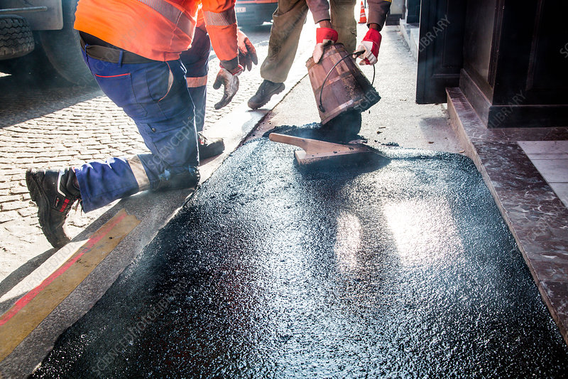 Workmen resurfacing a section of a sidewalk