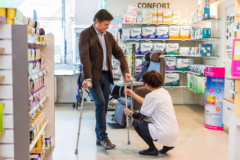 Man trying crutches in a pharmacy