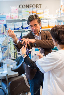Man trying an elbow support in a pharmacy