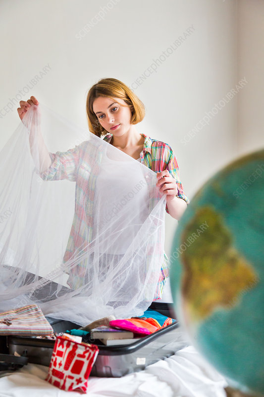 Woman putting a net in her suitcase