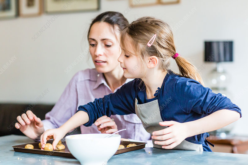 6 year-old girl learning cooking with her mother