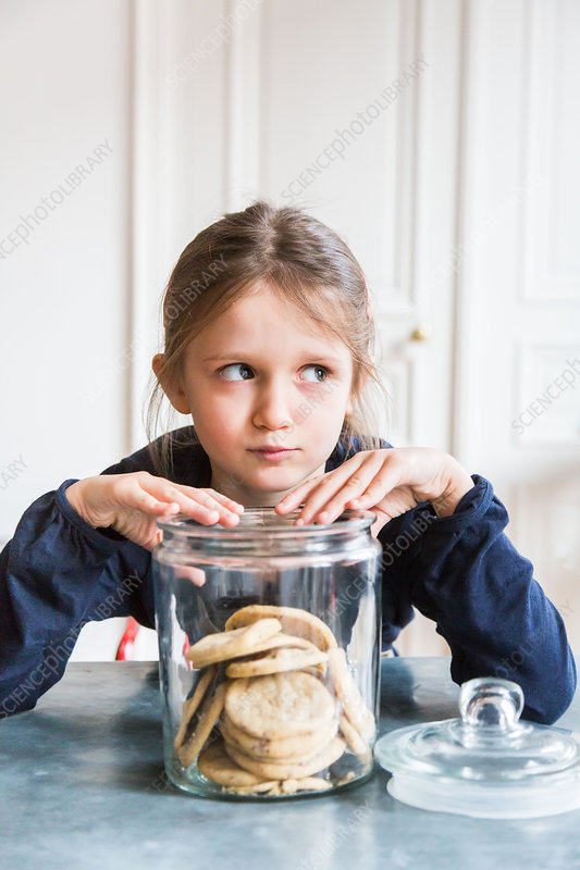 6 year-old girl reaching into a jar of cookies