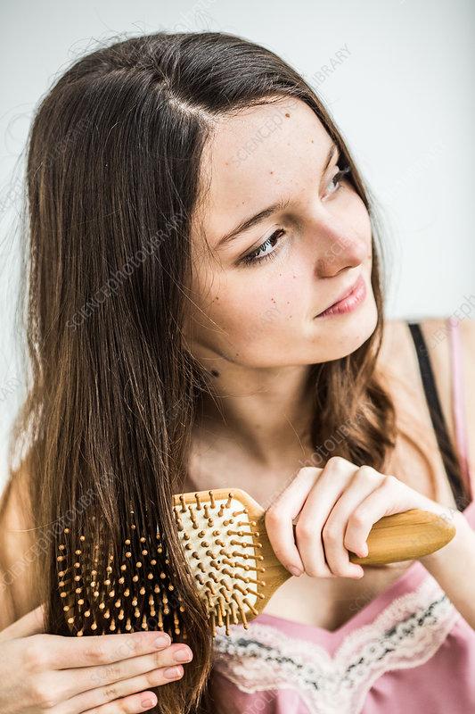 Teenage girl brushing her hair