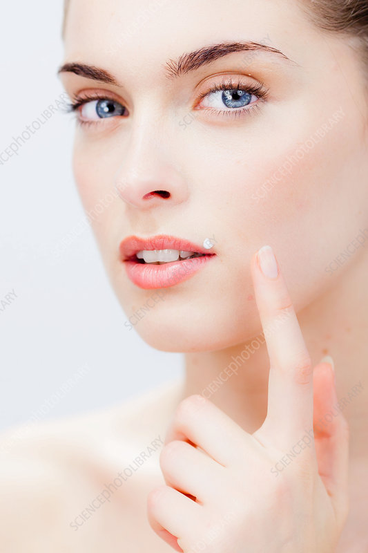 Woman applying cream on her lips