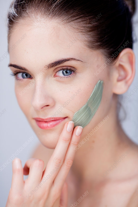 Woman applying green clay cosmetic beauty mask