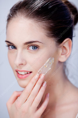Woman exfoliating her face with facial scrub treatment