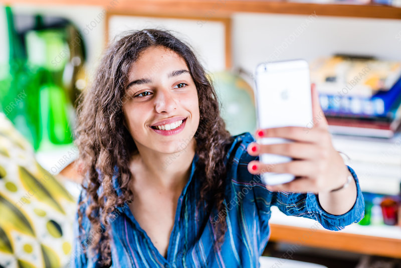 Teenage girl taking picture with camera phone
