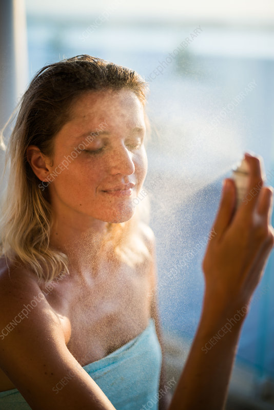 Woman spraying water on her face