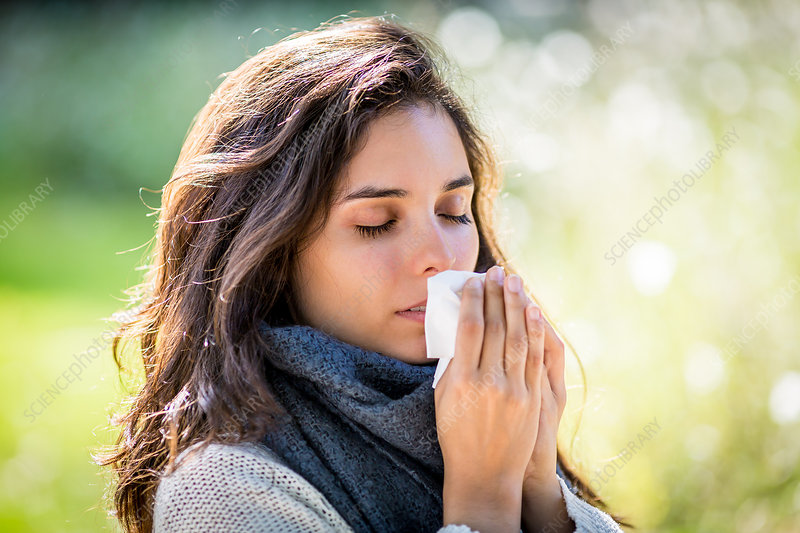 Woman with a cold using tissue