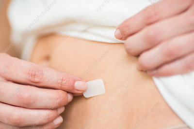 Woman applying a patch
