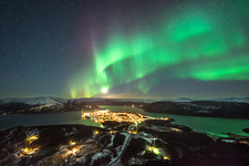 Aurora borealis over city lights
