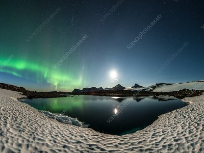 Moon and aurora borealis over a lake