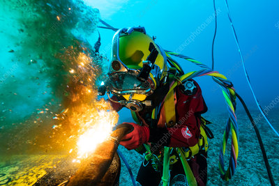 Industrial diver cutting metal underwater