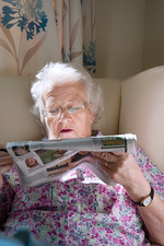 Care home resident reading newspaper