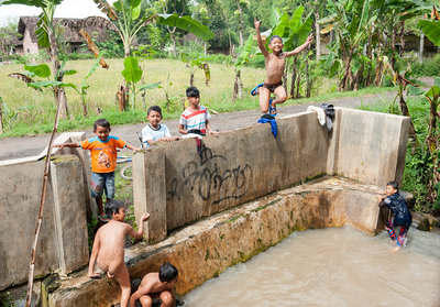 Children playing in watering hole, Bali