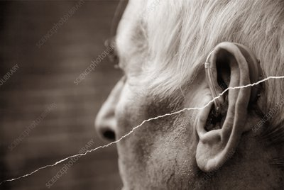 Elderly man using a hearing aid