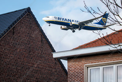 Passenger airliner flying over houses
