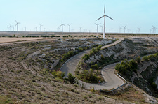 Wind turbines by a winding road