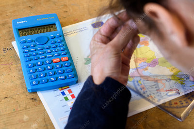 Student with a calculator, map and protractor