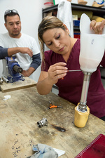 Disabled worker making prosthetic leg, Mexico