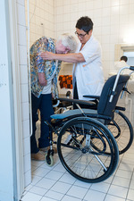 Nurse aiding an elderly woman to the toilet