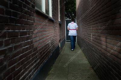 Nurse walking along an alley
