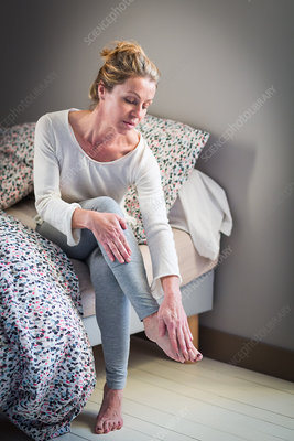 Woman suffering from an articular pain in the foot