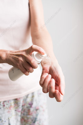 Woman applying an oestrogen gel on her hands